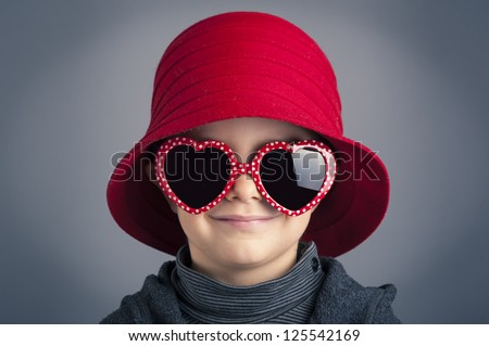 Portrait of smiling kid wearing heart glasses and red vintage hat over dark background. - stock photo
