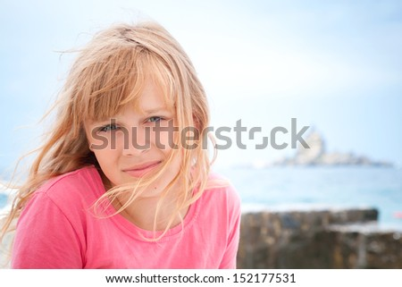 Portrait of smiling little blond girl in pink on the seacoast - stock photo