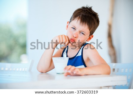 Portrait of smiling little boy refuses to eat delicious yogurt - stock photo