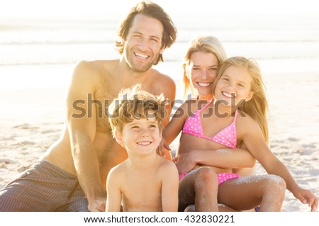 Portrait of smiling little boy with his family sitting in background at beach. Parents with children enjoying a holiday at the sea. - stock photo