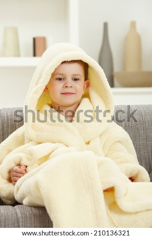 Portrait of smiling little caucasian boy in bathrobe sitting at home. Hood over head. - stock photo