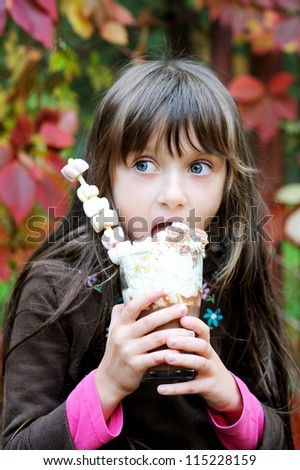 Portrait of smiling little cute girl with a glass of hot chocolate - stock photo