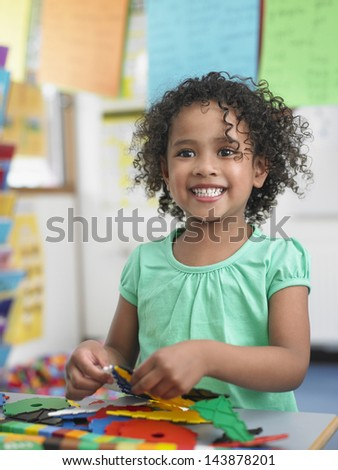 Portrait of smiling little girl assembling  puzzles in classroom - stock photo