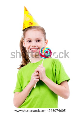 Portrait of smiling little girl in green t-shirt and party hat with colored candy - isolated on white. - stock photo