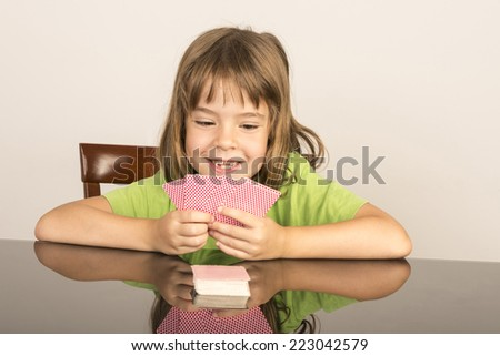 portrait of smiling little girl playing cards - stock photo