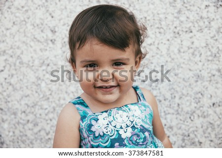Portrait of smiling lovely little girl looking at camera against of wall - stock photo