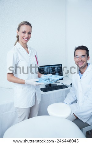 Portrait of smiling male and female dentists with computer monitor - stock photo