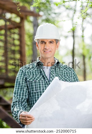 Portrait of smiling male architect holding blueprint at construction site - stock photo