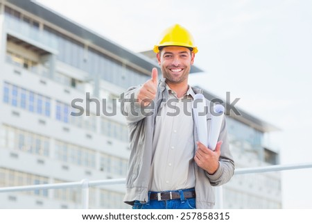 Portrait of smiling male architect with blueprints gesturing thumbs up outdoors - stock photo