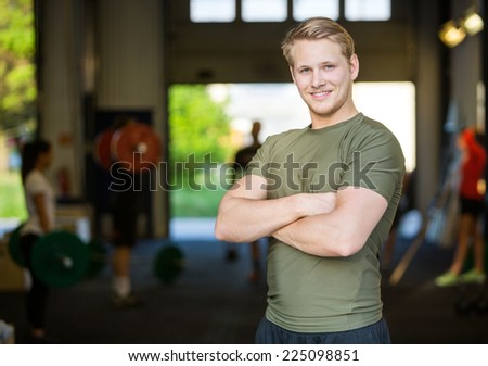 Portrait of smiling male athlete standing arms crossed at gym - stock photo