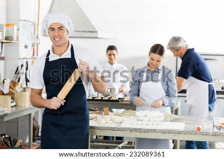 Portrait of smiling male chef holding rolling pin while colleagues preparing pasta at commercial kitchen
