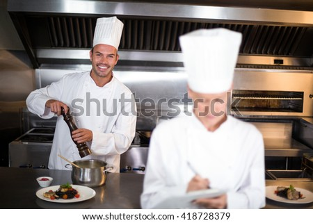 Portrait of smiling male chef preparing food in commercial kitchen - stock photo