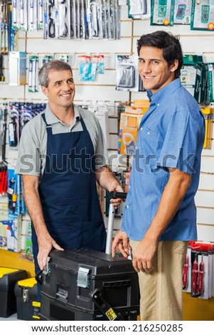 Portrait of smiling male customer buying tool case while salesman looking at him in hardware store