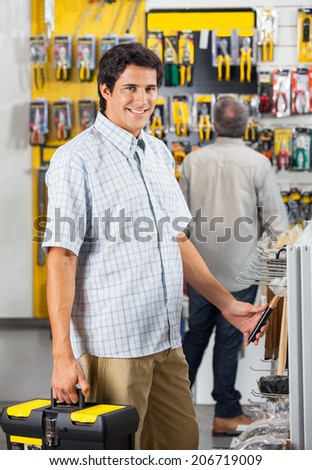 Portrait of smiling male customer purchasing tools with man in background at hardware shop