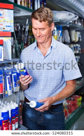 Portrait of smiling male customer selecting sealant bottle in housewares department