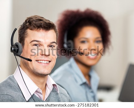Portrait of smiling male customer service representative with female colleague working in office - stock photo