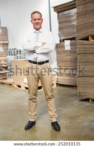 Portrait of smiling male manager with arms crossed in warehouse - stock photo