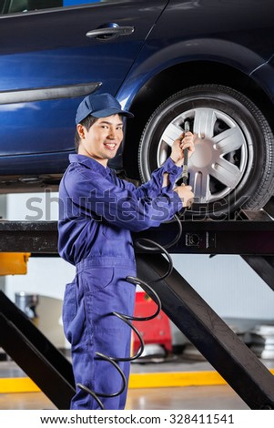 Portrait of smiling male mechanic filling air into car tire at garage - stock photo