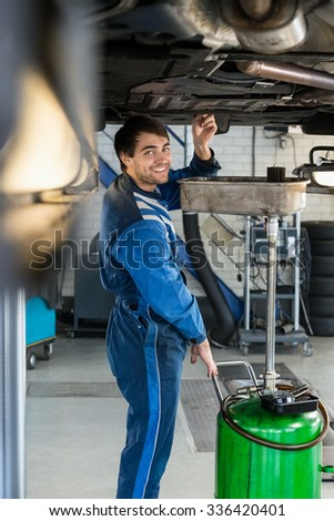 Portrait of smiling male mechanic repairing car on hydraulic lift in garage - stock photo