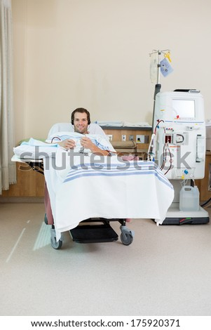 Portrait of smiling male patient listening music while receiving renal dialysis treatment in hospital room - stock photo