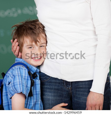 Portrait of smiling male student embraced his mother after school - stock photo