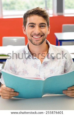 Portrait of smiling male student reading notes in classroom - stock photo
