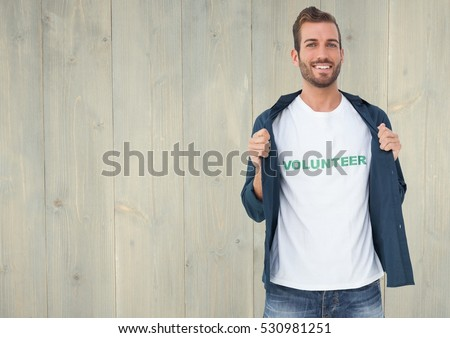 Portrait of smiling male volunteer standing against wooden background
