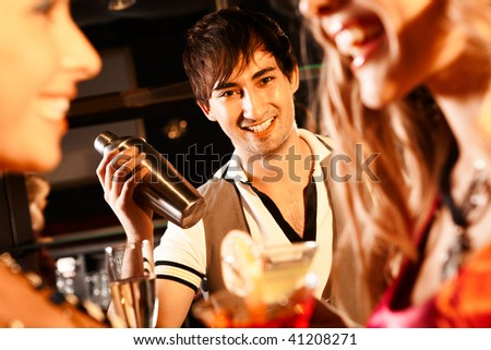 Portrait of smiling male with bottle looking at camera in the bar - stock photo