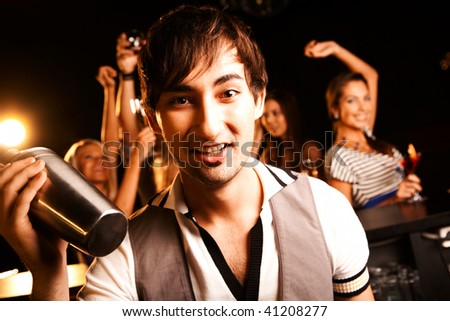 Portrait of smiling male with bottle looking at on background of dancers - stock photo