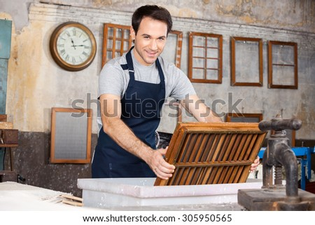 Portrait of smiling male worker dipping mold in pulp and water at paper factory - stock photo