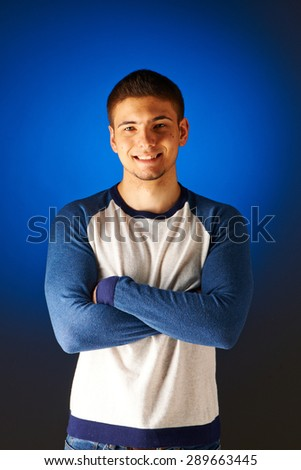 Portrait of smiling man against blue background - stock photo