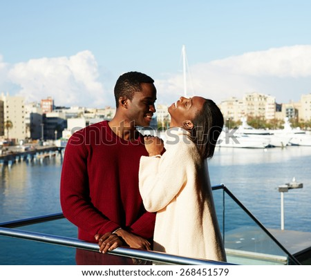 Portrait of smiling man and woman standing on the balcony with beautiful yacht port background during their spring holidays in Barcelona, happy couple enjoying vacation holiday outdoors - stock photo