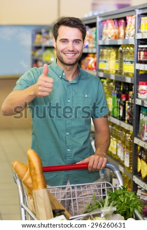 Portrait of smiling man buy products with his trolley and thumb up at supermarket - stock photo