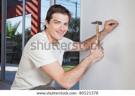 Portrait of smiling man hammering the wall with nail - stock photo