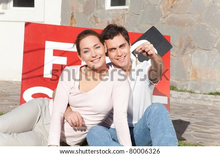 Portrait of smiling man holding keys with wife sitting on side - stock photo