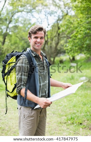 Portrait of smiling man holding map and standing in forest