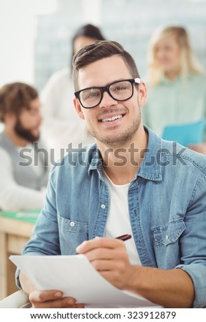 Portrait of smiling man holding paper and pen while working at office - stock photo