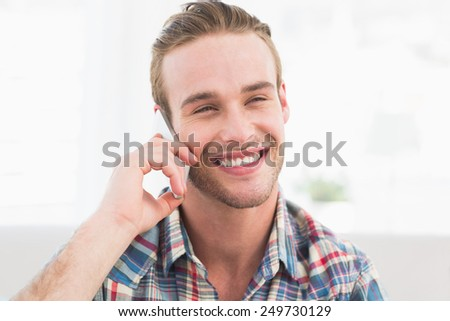 Portrait of smiling man on the phone at home in the living room - stock photo