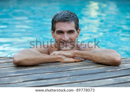 Portrait of smiling man relaxing by the swimming pool's edge - stock photo