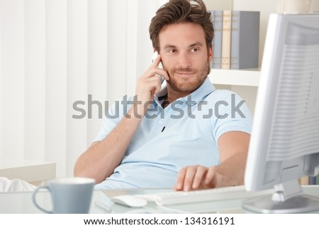 Portrait of smiling man speaking on mobile phone, sitting at desk, looking at computer screen. - stock photo
