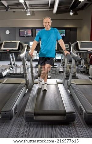 Portrait of smiling man standing on treadmill in health club