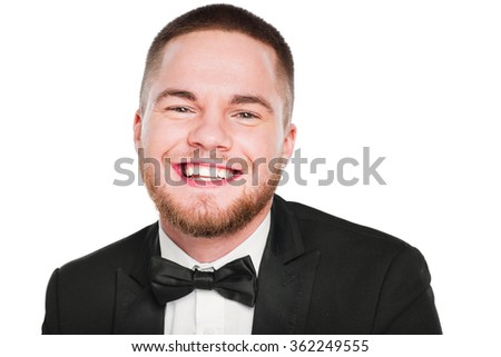 Portrait of smiling man wearing a tux with bow-tie on white background. - stock photo