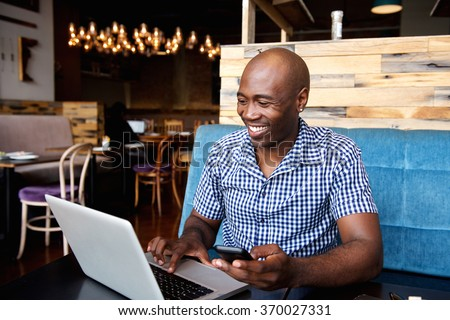 Portrait of smiling man with a mobile phone sitting at cafe using laptop - stock photo