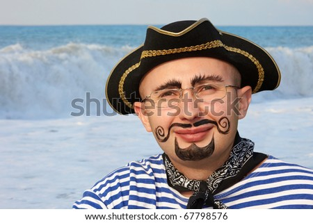 portrait of smiling man with drawed beard and whiskers in pirate suit. sea wave in out of focus. - stock photo