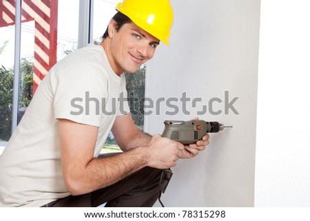 Portrait of smiling man worker with hard hat drilling wall - stock photo