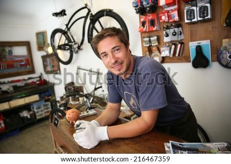 Portrait of smiling man working in bike rental shop - stock photo