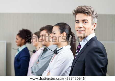 Portrait of smiling manager standing in row with team at call center - stock photo