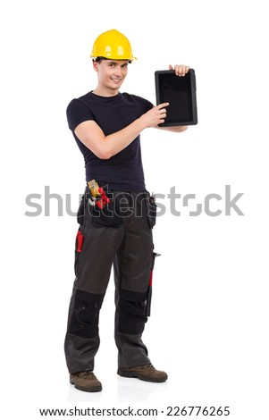 Portrait of smiling manual worker holding a digital tablet and pointing. Full length studio shot isolated on white.