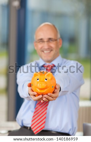 Portrait of smiling mature businessman holding piggy bank in office - stock photo