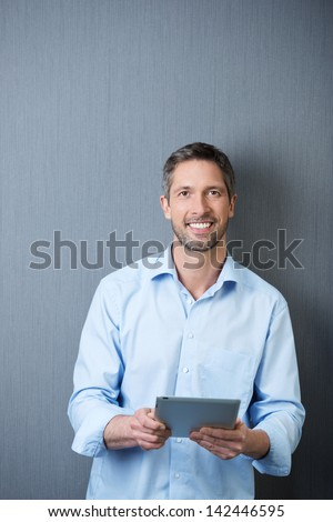 Portrait of smiling mature businessman holding tablet pc against blue wall - stock photo